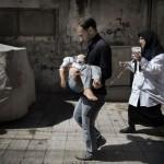 Un syrien portant sa fille devant un hôpital en Septembre